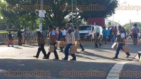 Xalapa, Ver., 30 de junio de 2016.- Las personas que est�n afuera del Congreso local salen y regresan al per�metro cercado por polic�as del IPAX con cajas de cart�n que contienen algunos alimentos.