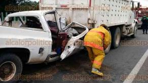 Medell�n de Bravo, Ver., 25 de julio de 2016.- La cabina de una camioneta Chevrolet blanca qued� destrozada tras el choque contra un cami�n de volteo. El conductor fue liberado del veh�culo por rescatistas de la Cruz Roja y elementos de PC, para ser trasladado al Hospital Regional