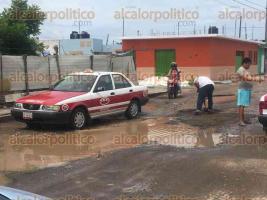 Veracruz, Ver., 25 de julio de 2017.- La calle Guacamaya, en el fraccionamiento Albatros presenta hundimientos y encharcamientos, ante la falta de apoyo de la autoridad, colonos rellenan con tierra y escombros para poder transitar.