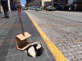 """Xalapa, Ver., 18 de septiembre de 2018.- Registro destapado en banqueta de la calle Lucio, en Centro de la cuidad, sólo colocaron un cartón con el letrero """"cuidado"""" para prevenir a peatones."""