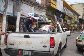 Xalapa, Ver., 21 de agosto de 2019.- Trabajadores del Ayuntamiento de Xalapa levantaron un puesto de calcetas a vendedora ambulante. Esto provocó que, en plena calle Revolución, comerciantes y transeúntes se subieran a la camioneta donde se llevaban la mercancía para rescatarla.