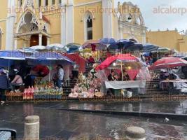Xalapa, Ver., 23 de octubre de 2019.- La fuerte lluvia registrada la tarde de este miércoles en la ciudad no ahuyentó a los comerciantes que se instalaron en la Catedral, a la espera de cientos de peregrinos por las festividades de San Rafael Guízar.