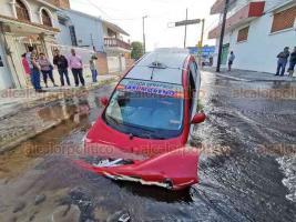 Veracruz, Ver., 16 de febrero de 2020.- Un taxi cayó dentro de un hundimiento ubicado en Collado y 20 de noviembre, provocado por una macro fuga de agua de una tubería. El vehículo registró fuertes pérdidas materiales, el conductor resultó ileso.