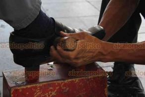 """Xalapa, Ver., 2 de junio de 2020.- Víctor Hernández Morales, quien lleva 35 años """"boleando"""" zapatos en el parque Juárez, cerrado por contingencia, no puede quedarse en casa pues debe llevar sustento a su familia. Ahora, ubicado en pasillos del edificio """"Nachita"""", dice que le va mejor, ya que hay días que hace hasta 6 boleadas."""