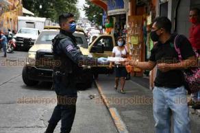 """Xalapa, Ver., 8 de julio de 2020.- Este miércoles, elementos de la Policía Municipal continuaron entregando cubrebocas a transeúntes y conductores de taxis, en la zona aledaña al Mercado """"Jáuregui""""."""