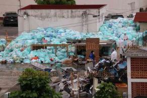 Veracruz, Ver., 12 de agosto de 2020.- Personal con trajes de protección agrupa las numerosas bolsas de basura ubicadas en el estacionamiento de la Clínica 14 del IMSS. Según médicos, se trata de desechos peligrosos, incluido material usado para COVID-19.