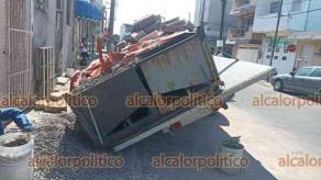 Veracruz, Ver., 27 de septiembre de 2021.- Camión que transportaba blocks se hundió en el pavimento y tiró parte de la carga sobre la acera frente a vivienda en las calles de la colonia Flores Magón. No se reportaron lesionados.